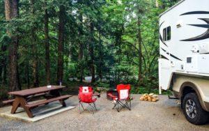 Campground in Kanada mit Feuerstelle und Campingchairs neben einem Truck Camper