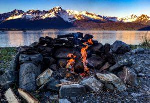 Feuerstelle aus Steinen vor Meer und Bergen