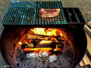 Steak auf einem Grillrost über einem Feuer in einer Feuerstelle
